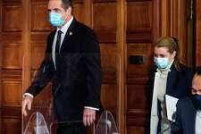 Gov. Andrew Cuomo, left, enters a coronavirus press briefing with aide Melissa DeRosa, center, on Wednesday, Feb. 10, 2021, at the Capitol in Albany, N.Y. (Office of the Governor)