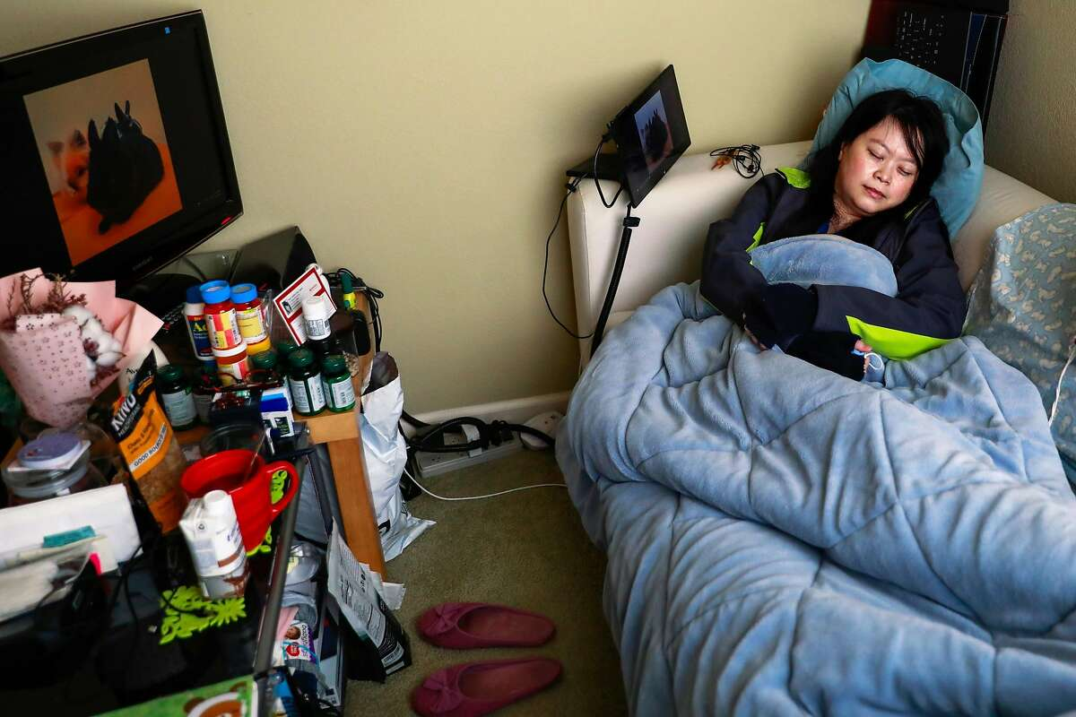 Joy Wu, 37, who has been plagued with COVID-19 symptoms since she came back from a trip to the Galapagos in March, rests on her couch on Monday, Feb. 15, 2021 in San Carlos, California. She hasn't been able to do much in nearly a year and had to quit her job as a medical device engineer.