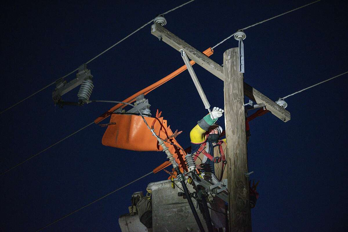 Oncor apprentice lineman Brendan Waldon repairs a utility pole that was damaged by the winter storm that passed through Texas Thursday, Feb. 18, 2021, in Odessa, Texas. (Eli Hartman/Odessa American via AP)