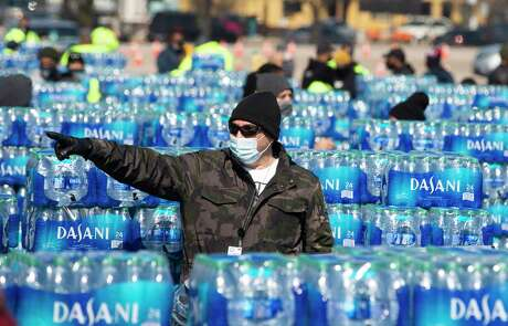 Volunteers help distributing free bottled water at a mass distribution Friday, Feb. 19, 2021, at Delmar Stadium in Houston. The city is still under boil water order and some places are still having low water pressure.