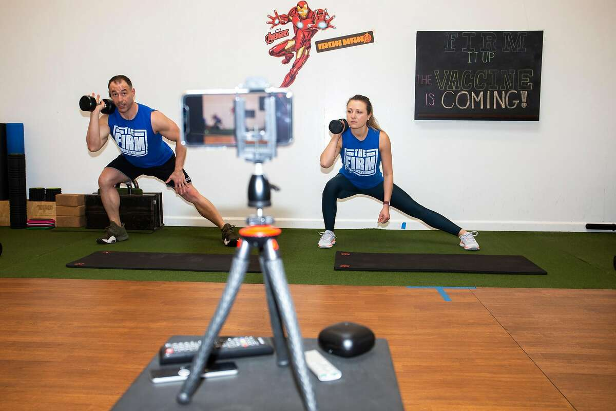 Personal trainers JJ Miller (left) and Justyn Sproull record a Zoom workout class in Cole Valley, S.F.