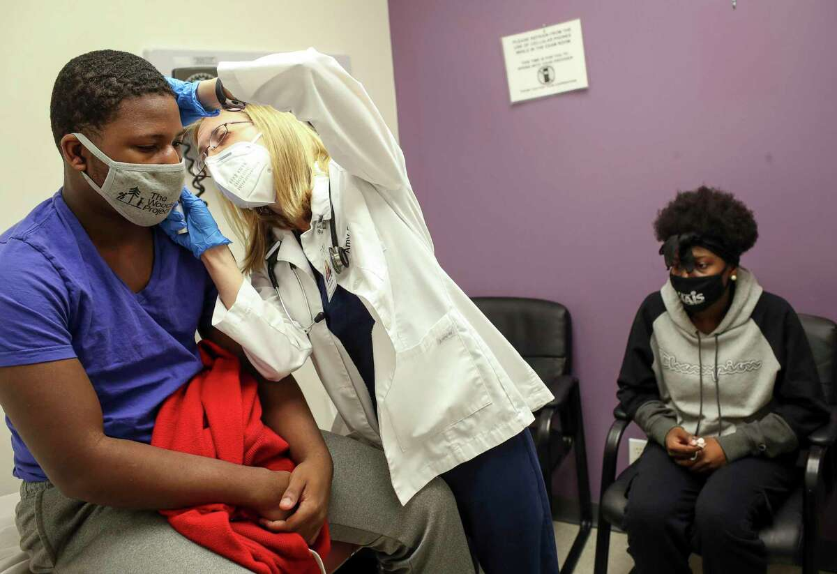 Adonye Williams, 16, gets a brief exam by Amy Starr, a family nurse practitioner, as his sister Animi Williams, 14, waits for hers Saturday, Feb. 13, 2021, at CyFair Clinical Research Center in Houston. The siblings volunteered to be part of a Moderna vaccine trial for teenagers.