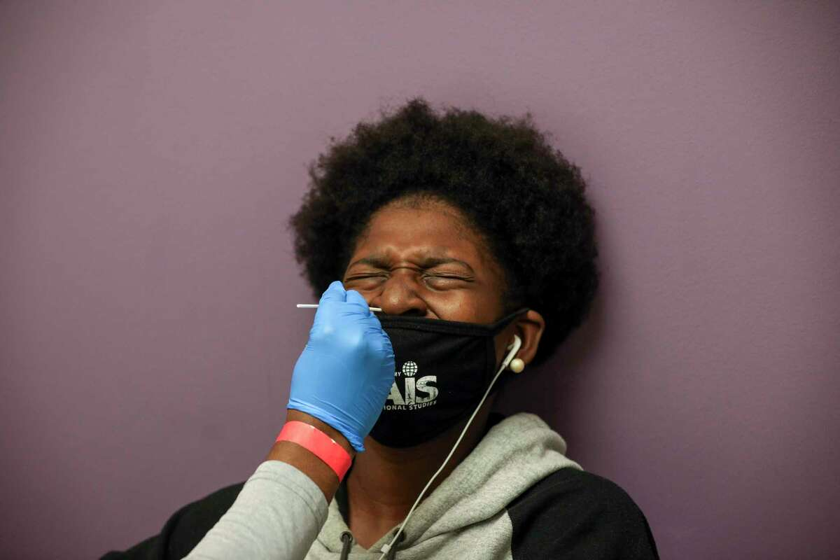 Animi Williams, 14, reacts as she has a nasal swab performed as part of a Moderna vaccine trial for teenagers Saturday, Feb. 13, 2021, at CyFair Clinical Research Center in Houston.
