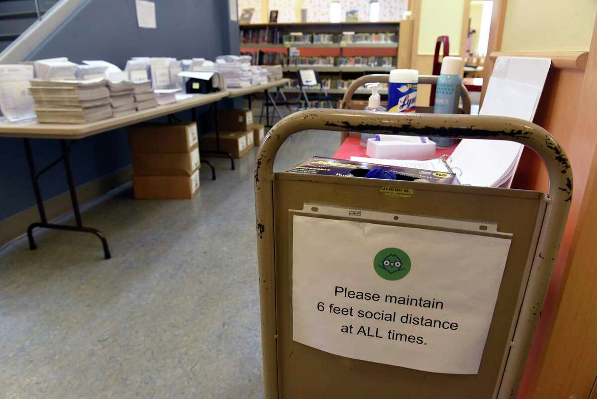 A social distance sign is taped on a PPE cart and tax forms are seen at left at the Albany Library Pine Hills Branch on Friday, Feb. 19, 2021 in Albany, N.Y. Library directors are advocating for their staff to become eligible for vaccinations. (Lori Van Buren/Times Union)