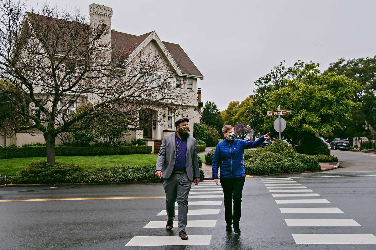 City Council members Terry Taplin, left, and Lori Droste walk through a gated neighborhood in Berkeley, Calif., zoned for single-family housing on Friday, Feb. 19, 2021.