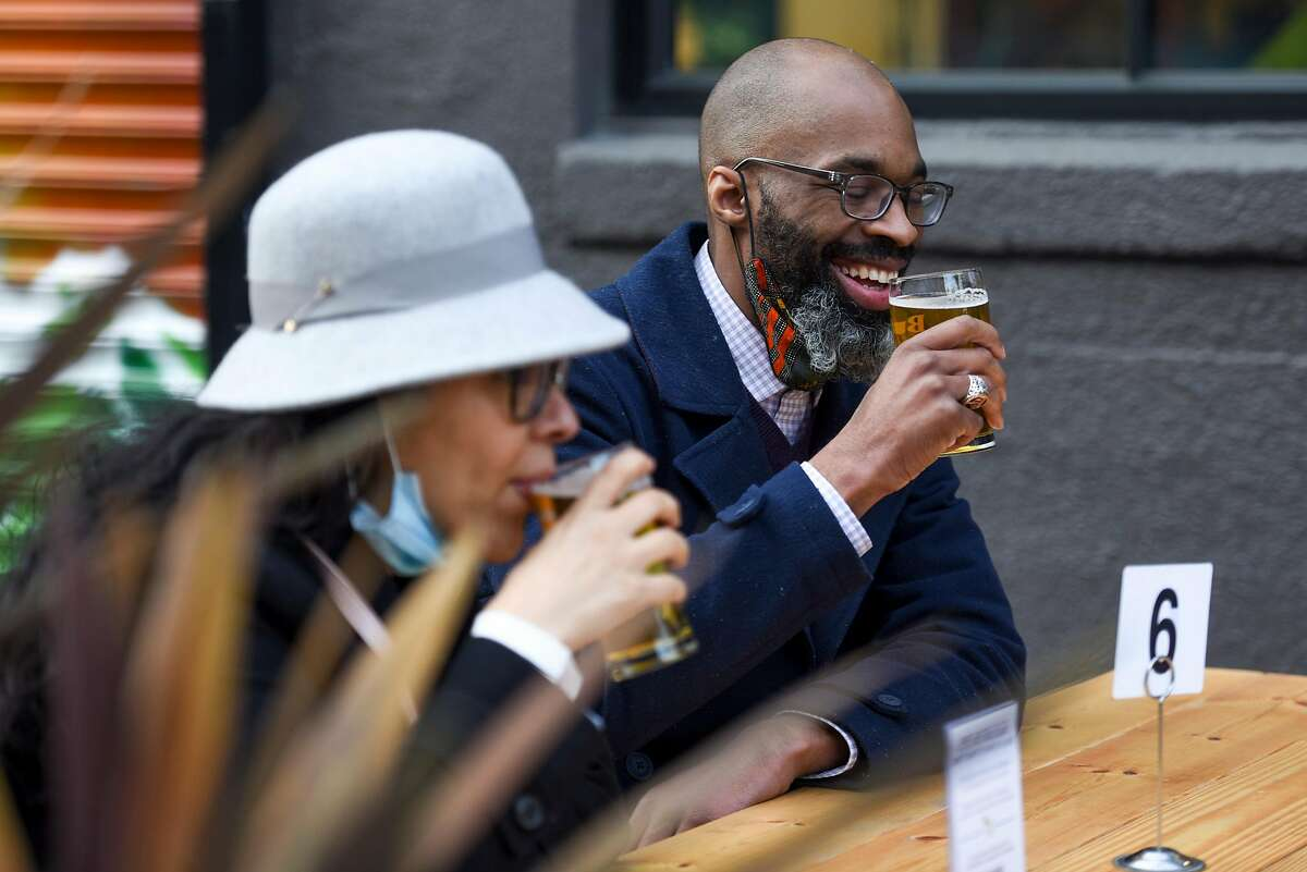 Jennie Medina and Ian King II, both of Oakland, sip on pale ales at Buck Wild Brewing in Oakland on Thursday. Under new guidance, breweries and distilleries may open outdoors in purple and red tiers even if they do not serve meals.