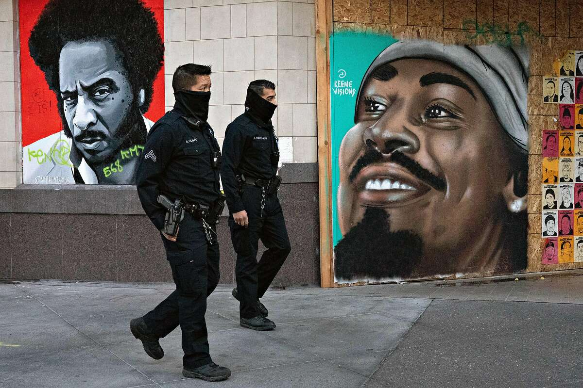 OPD officers Bryant Ocampo and Daniel Cornejo-Valdivia patrol downtown on Thursday, Dec. 17, 2020 in Oakland. Several Oakland City Council members proposed Monday cutting about $18.4 million from the Oakland Police Department to fund violence prevention and social services.