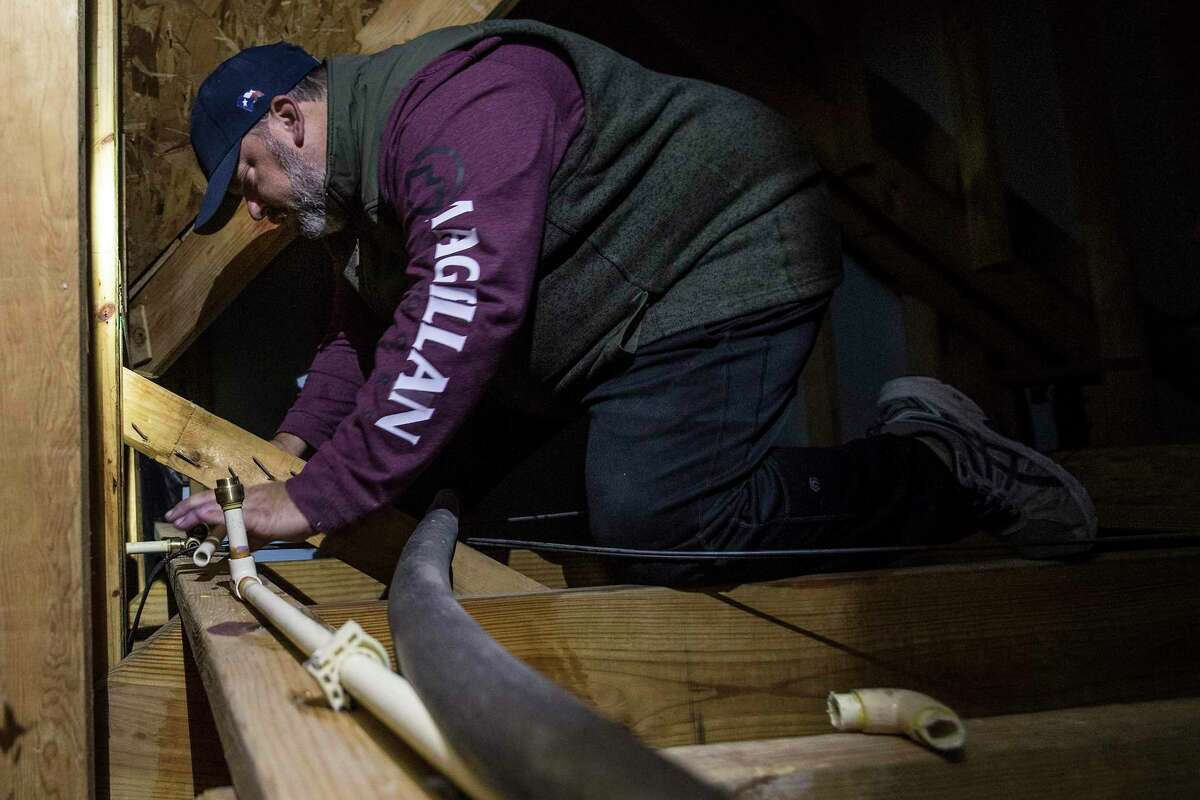 Chris Jackson replaces a broken water line in a friend's house after the pipe froze overnight Wednesday in Spring.