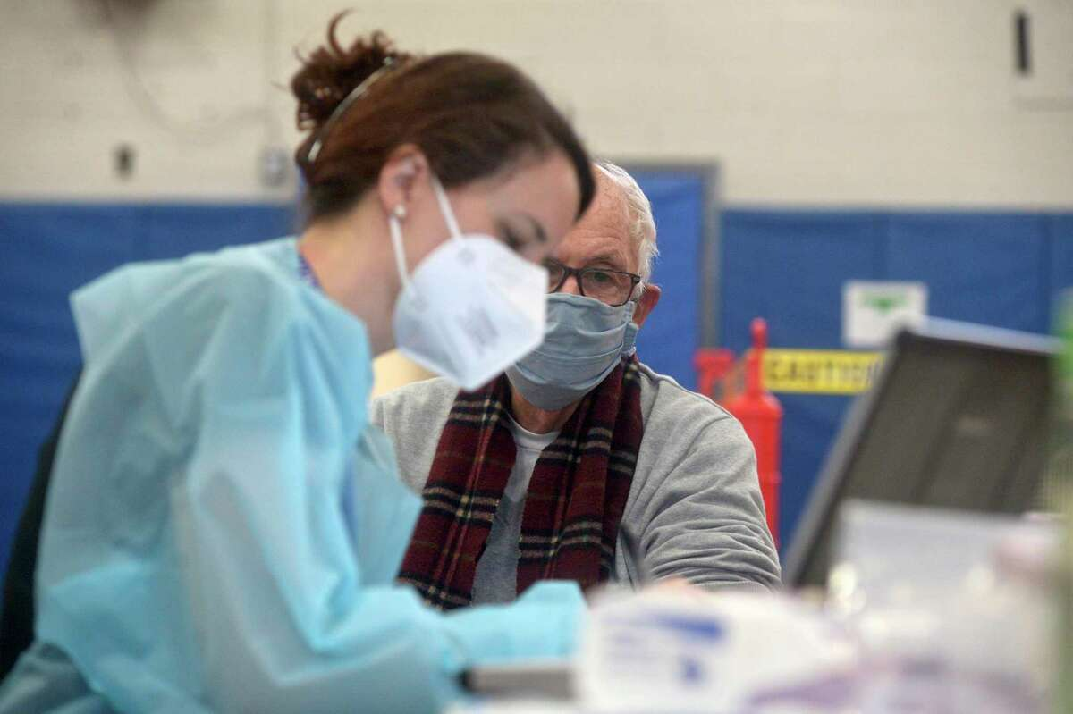 Bridget Bethray RN, with RVNAhealth takes information before administering a COVID-19 vaccine to Sherwin Gorenstein, of Ridgefield, in the RVNA clinic in the Yanity Gym, on Thursday morning, February 4, 2021, in Ridgefield, Conn.