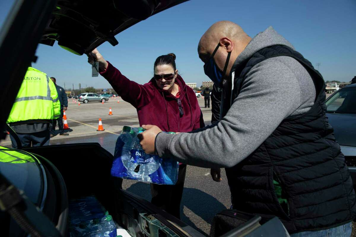 Steven Alexander, of Houston Municipal Courts, puts cases of free bottled water into Kimberly Caldwell's trunk at a mass distribution Friday, Feb. 19, 2021, at Delmar Stadium in Houston. Caldwell said she was very grateful for the distribution. The city is still under boil water order and some places are still having low water pressure.