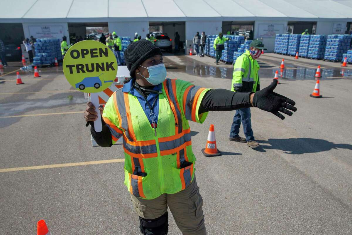 Dee Harris, of Houston Department of Neighborhoods, directing traffic at a free bottled water mass distribution Friday, Feb. 19, 2021, at Delmar Stadium in Houston. The city is still under boil water order and some places are still having low water pressure.