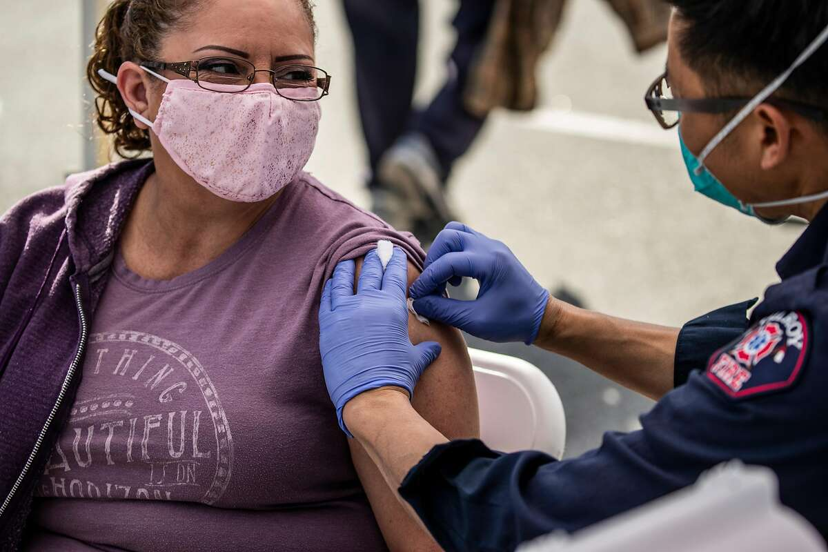Patricia Lugo looks toward firefighter-paramedic William Nguyen of the Gilroy Fire Department as Nguyen prepares to administer a dose of Moderna COVID-19 vaccine at the Gilroy Senior Center.