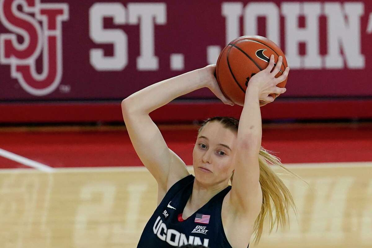 Connecticut guard Paige Bueckers (5) looks to pass as she keeps the ball from a St. John's' defender on Wednesday.