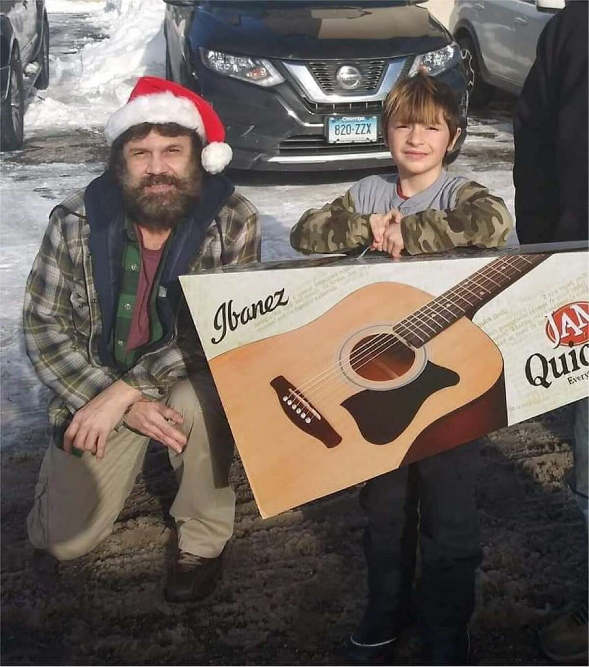 Vinny Rodriguez has been giving away guitars during the COVID-19 pandemic as a way to keep children busy and interested in music. He is pictured here with a child named Logan.