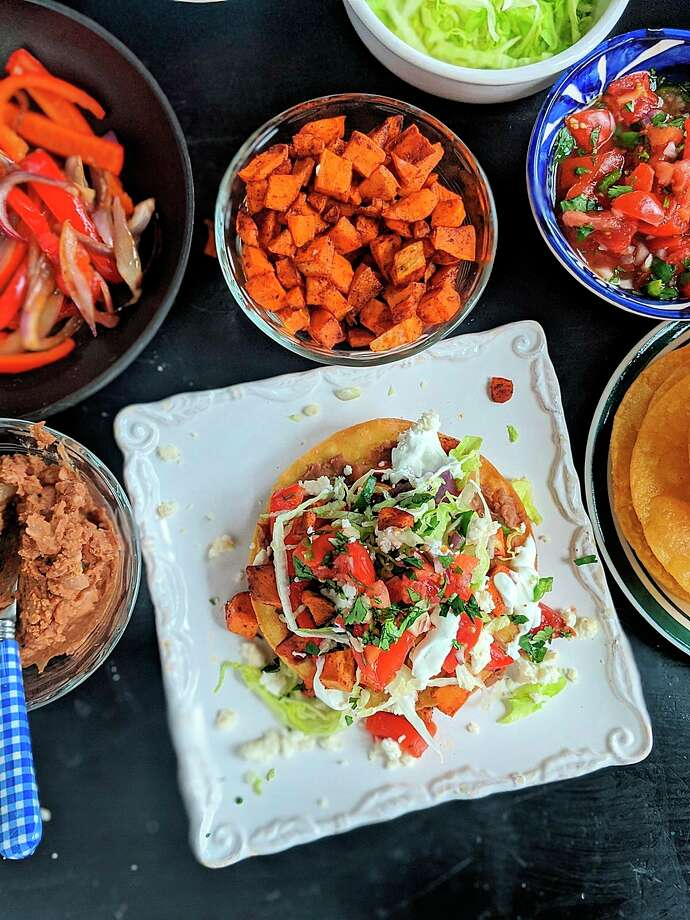 These vegetarian tostadas are stacked with two layers of smashed pinto beans, lettuce, pico and roasted sweet potatoes and bell peppers. Crumbled queso fresco and lime crema add the crowning touch. (Gretchen McKay/TNS) / Pittsburgh Post-Gazette