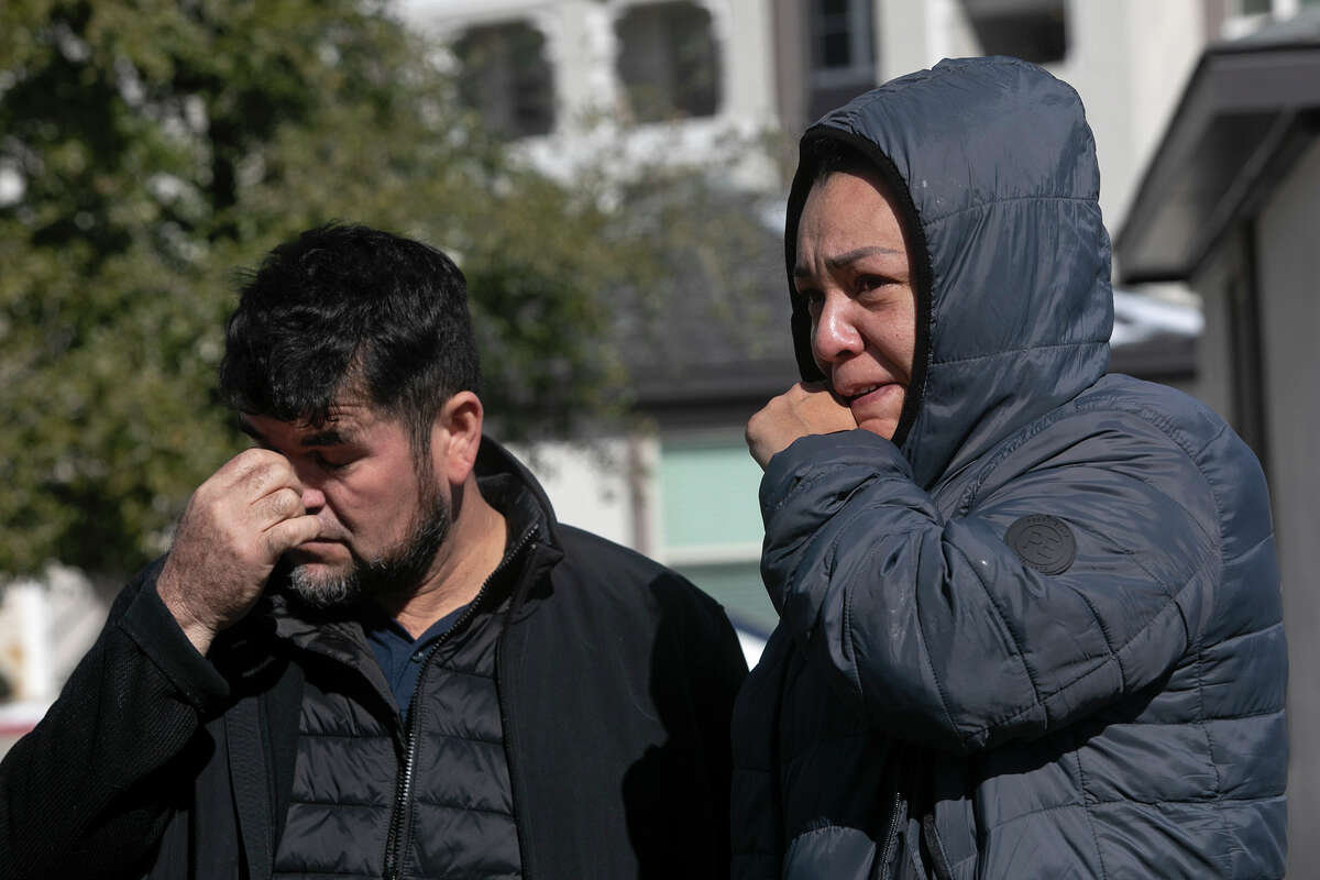 Aziel Reyes and Felix Solano Castro view the smoldering remains of what was their apartment building at the Cortland View at TPC apartment complex in San Antonio on Feb. 19, 2021. Reyes and Castro, along with their three children, lost everything in the fire Thursday night.