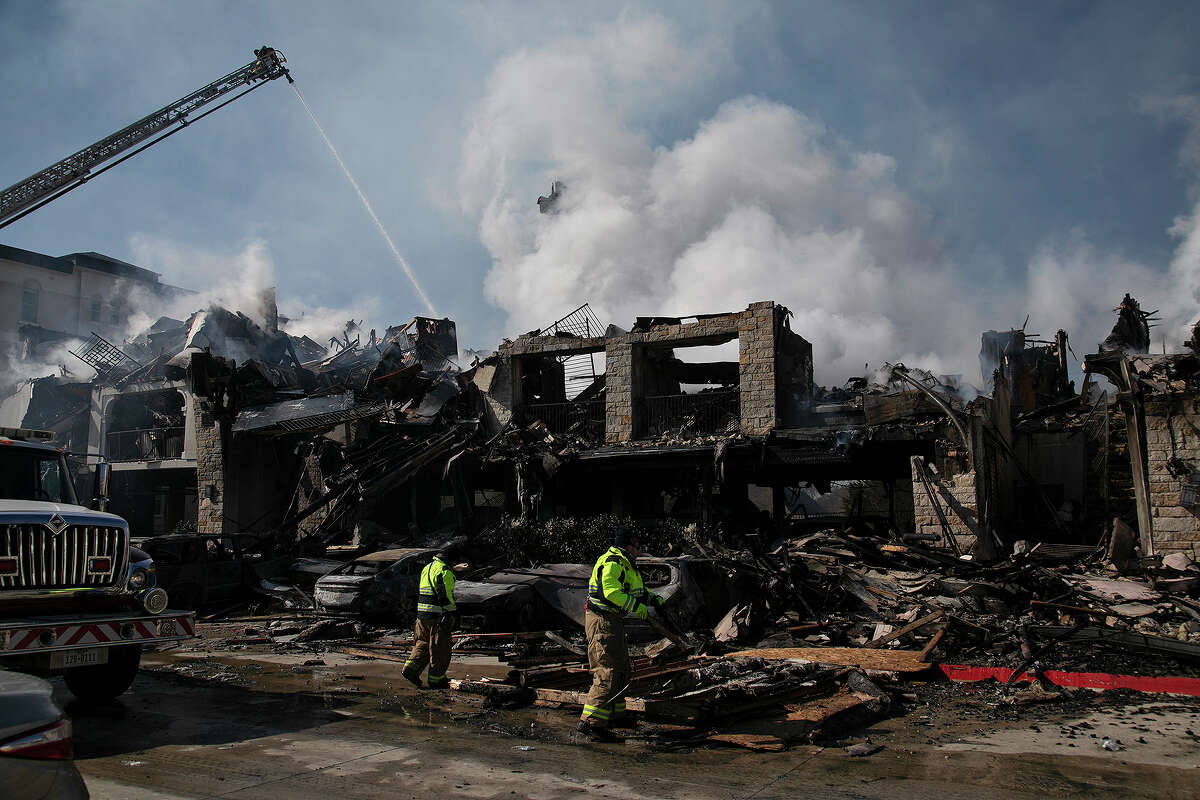 Members of the Bexar-Bulverde Volunteer Fire Department move debris in the aftermath of the previous night's fire at the Cortland View at TPC apartment complex in San Antonio on Feb. 19, 2021.