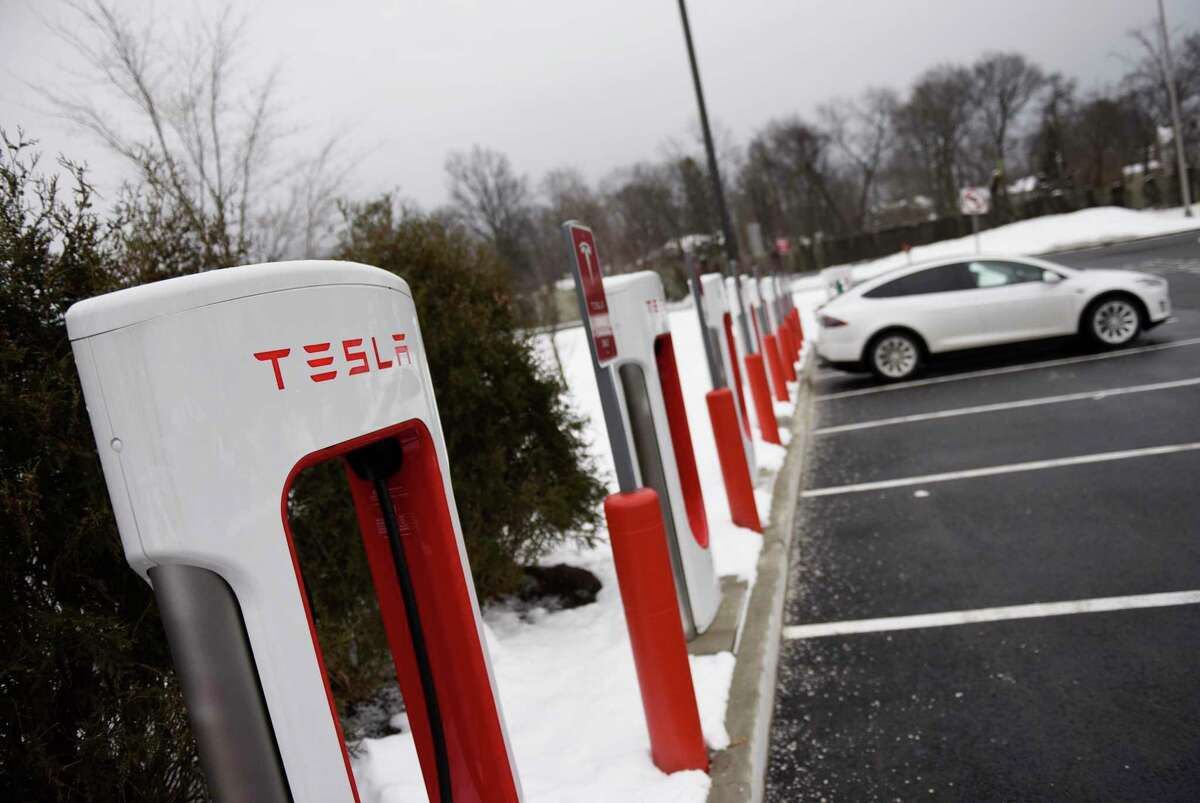 A Tesla electric vehicle charges at one of the high-speed charging ports at the I-95 southbound service plaza in Darien, Conn., on Feb. 9, 2021. Connecticut is looking to expand access to electric vehicles such as Tesla models by improving its EV subsidies program.
