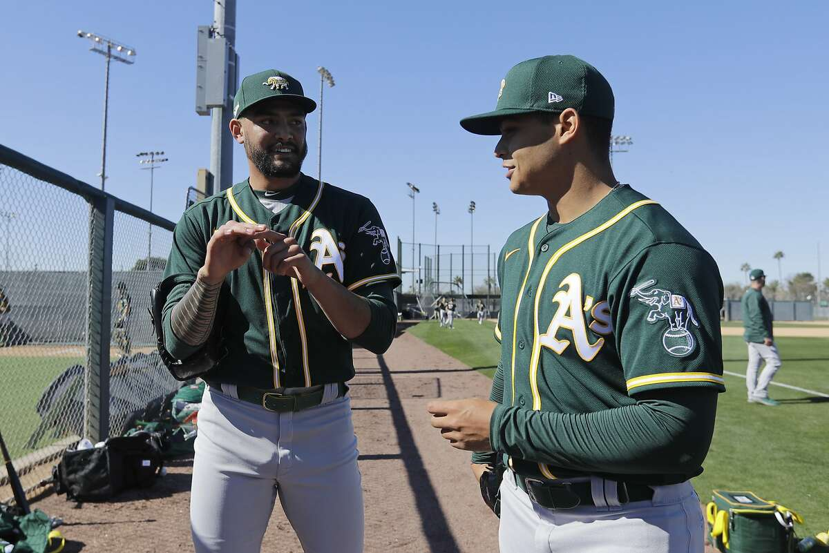 Oakland Athletics' Sean Manaea, left, talks with Jesus Luzardo during spring training baseball practice, Thursday, Feb. 13, 2020, in Mesa, Ariz. (AP Photo/Darron Cummings)