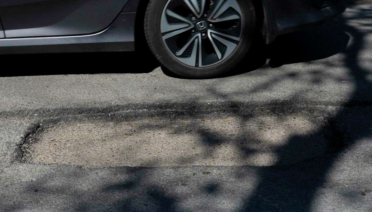 A driver passes by a cracked segment of 20th Street between Durham and Shepherd Drives on Feb. 19, 2021, near the Heights in Houston.