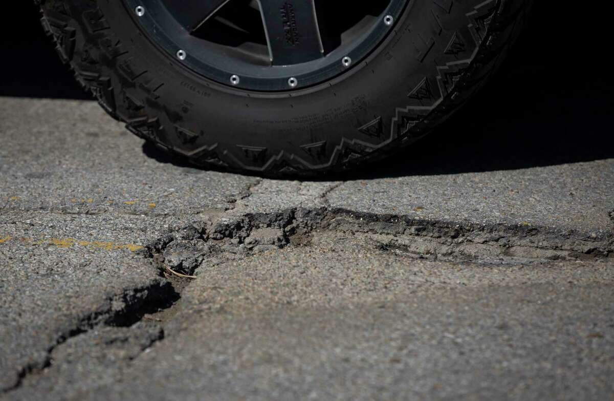 A driver passes by a pothole along 20th Street between Durham and Shepherd Drives on Feb. 19, 2021, near the Heights in Houston.