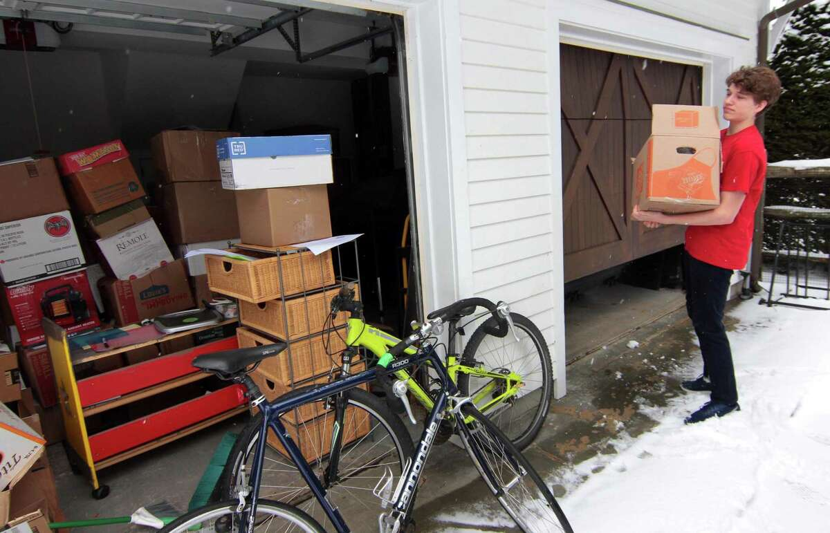 Brooks Barry, 17, who has been nationally recognized for his charitable efforts to, among other things, provide books to the needy across the globe, prepares a shipment of books in his garage in Southport, Conn., on Friday Feb. 19, 2021.