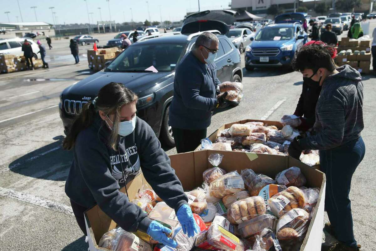 Lilia Alvarado joins her family volunteering at a San Antonio Food Bank distribution at Gustafson Stadium, Friday, Feb. 19, 2021. Close to 2,000 families registered for food at the stadium.