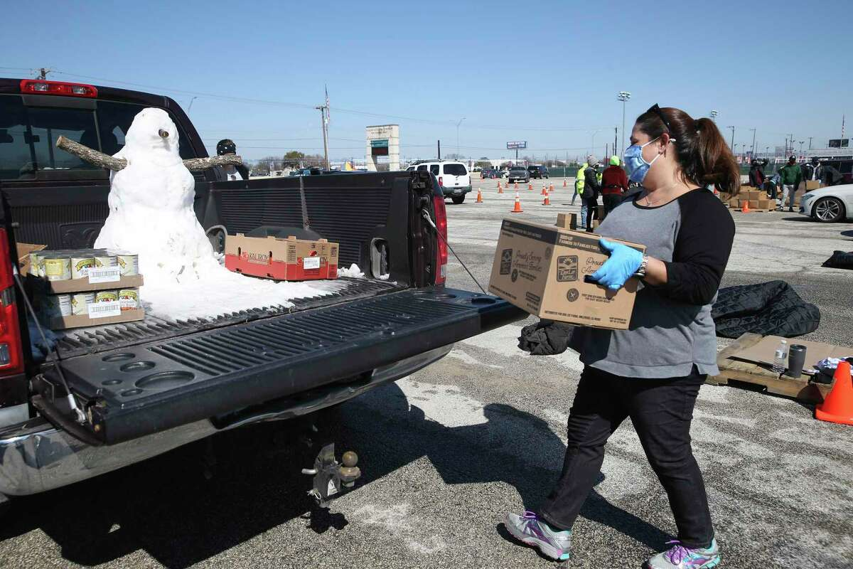 Elleana Saloman loads a box of food during a San Antonio Food Bank distribution at Gustafson Stadium and at the food bank, Friday, Feb. 19, 2021. Close to 2,000 families registered for food at the stadium.