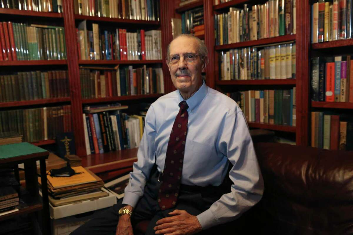 Dr. Joe Pierce sits in the library of his Sonterra home, Thursday, Feb. 11, 2021. Pierce and his wife, art patron, Aaronetta, have been organizing his vast book collection.
