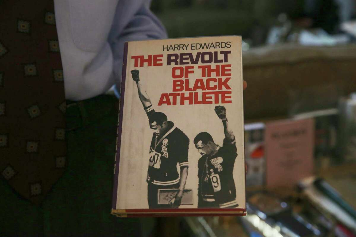 """Dr. Joe Pierce holds a copy of his favorite book, """"The Revolt of the Black Athlete,"""" by Harry Edwards, at his Sonterra home, Thursday, Feb. 11, 2021. Pierce and his wife, art patron, Aaronetta, have been organizing his vast book collection. Pierce was able to get the book autographed Edwards and the 1968 Olympian featured on the cover, Tommie Smith and John Carlos."""