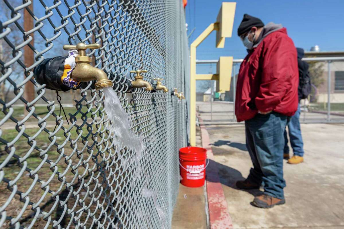 Eddie Gomez waits Friday, Feb. 19, 2021 for his five gallon buckets to fill with water at one of the San Antonio Water System's free water distribution locations.