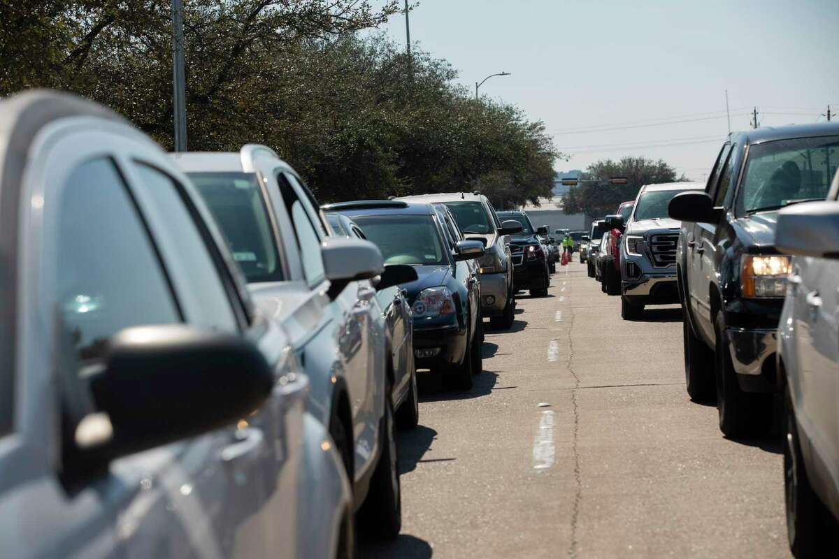 Houston residents wait in line to get free bottled water at a mass distribution Friday, Feb. 19, 2021, at Delmar Stadium in Houston. The city is still under boil water order and some places are still having low water pressure.