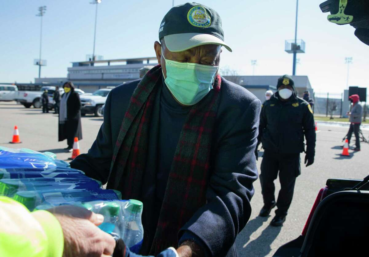 Houston Mayor Sylvester Turner helps distributing free bottled water at a mass distribution Friday, Feb. 19, 2021, at Delmar Stadium in Houston. The city is still under boil water order and some places are still having low water pressure.