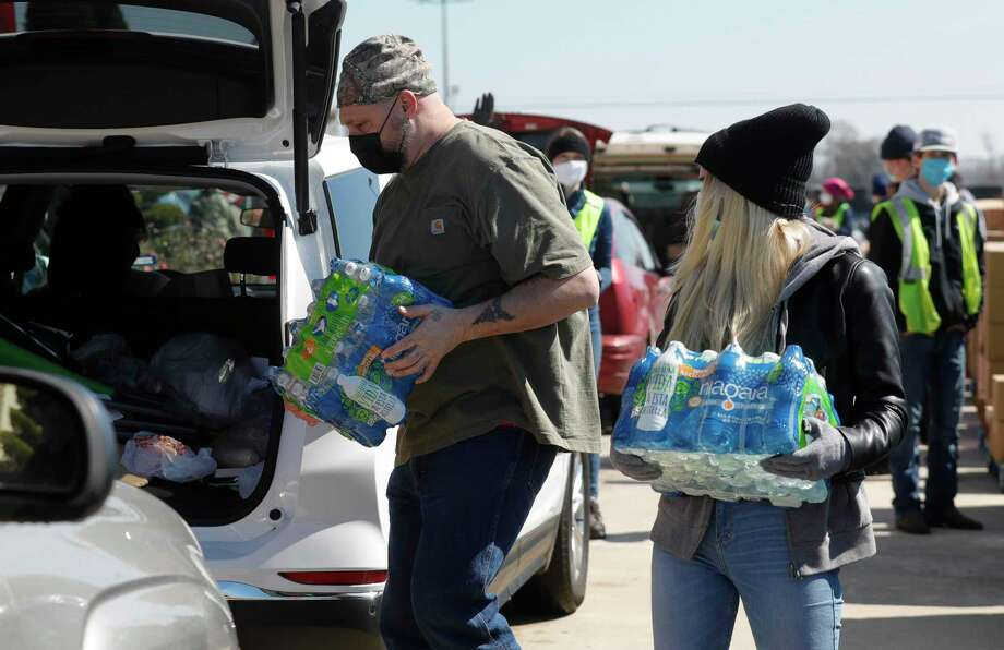 Brian Cook carries a package of water as volunteers distribute food and water to 600 families in need at the North Montgomery County Community Center, Friday, Feb. 18, 2021, in Willis. Many residents have been without power and water since Sunday and the mobile market provided in partnership with the Montgomery County Assistance Center and the Montgomery County Food Bank provided families with water and shelf-stable food. Photo: Jason Fochtman, Houston Chronicle / Staff Photographer / 2021 © Houston Chronicle