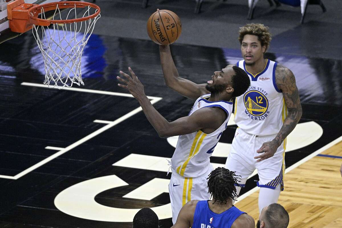 Golden State Warriors forward Andrew Wiggins goes up for a shot in front of Orlando Magic center Khem Birch, below, as Warriors guard Kelly Oubre Jr. (12) watches during the second half of an NBA basketball game, Friday, Feb. 19, 2021, in Orlando, Fla. (AP Photo/Phelan M. Ebenhack)