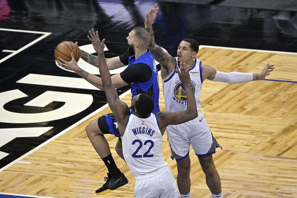 Orlando Magic guard Evan Fournier goes up for a shot between Golden State Warriors forward Andrew Wiggins (22) and forward Juan Toscano-Anderson, right, during the first half of an NBA basketball game, Friday, Feb. 19, 2021, in Orlando, Fla. (AP Photo/Phelan M. Ebenhack)