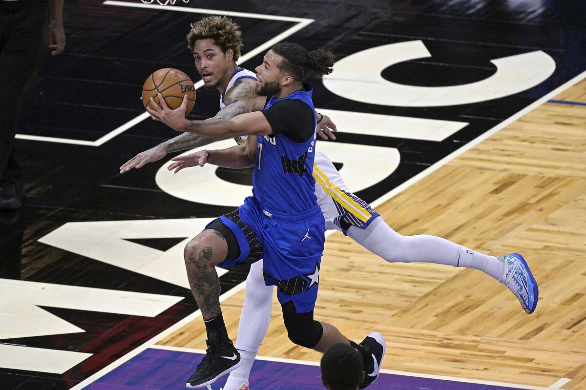 Orlando Magic guard Michael Carter-Williams (7) goes up for a shot in front of Golden State Warriors guard Kelly Oubre Jr. during the first half of an NBA basketball game, Friday, Feb. 19, 2021, in Orlando, Fla. (AP Photo/Phelan M. Ebenhack)