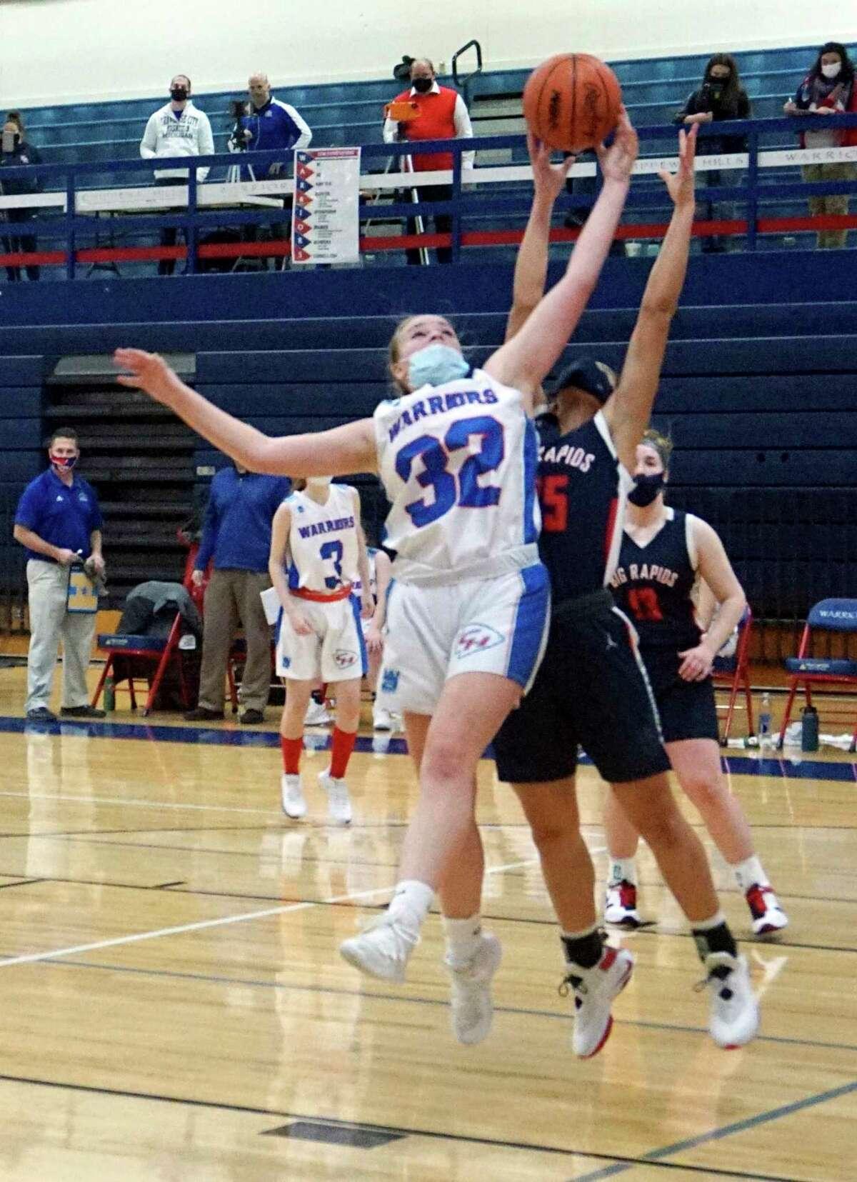 Chippewa Hills junior Madison Wrisley and Big Rapids freshman Marissa Warren go vertical for a rebound during a game on Friday night at Chippewa Hills High School. (Pioneer photo/Joe Judd)