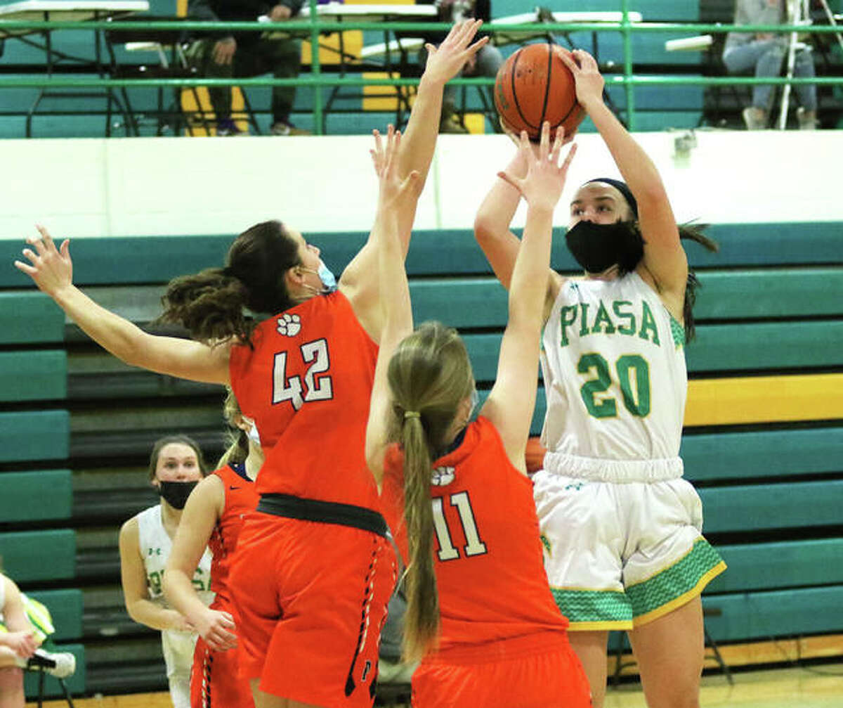 Southwestern's Korrie Hopkins (20) shoots over Pana's Jillian Hamilton (42) and Kylie Hendrickson (11) in the second half of a South Central Conference girls basketball game Friday night in Piasa.