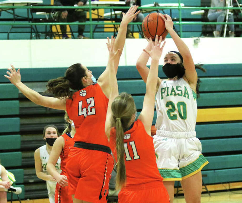 Southwestern's Korrie Hopkins (20) shoots over Pana's Jillian Hamilton (42) and Kylie Hendrickson (11) in the second half of a South Central Conference girls basketball game Friday night in Piasa. Photo: Greg Shashack / The Telegraph