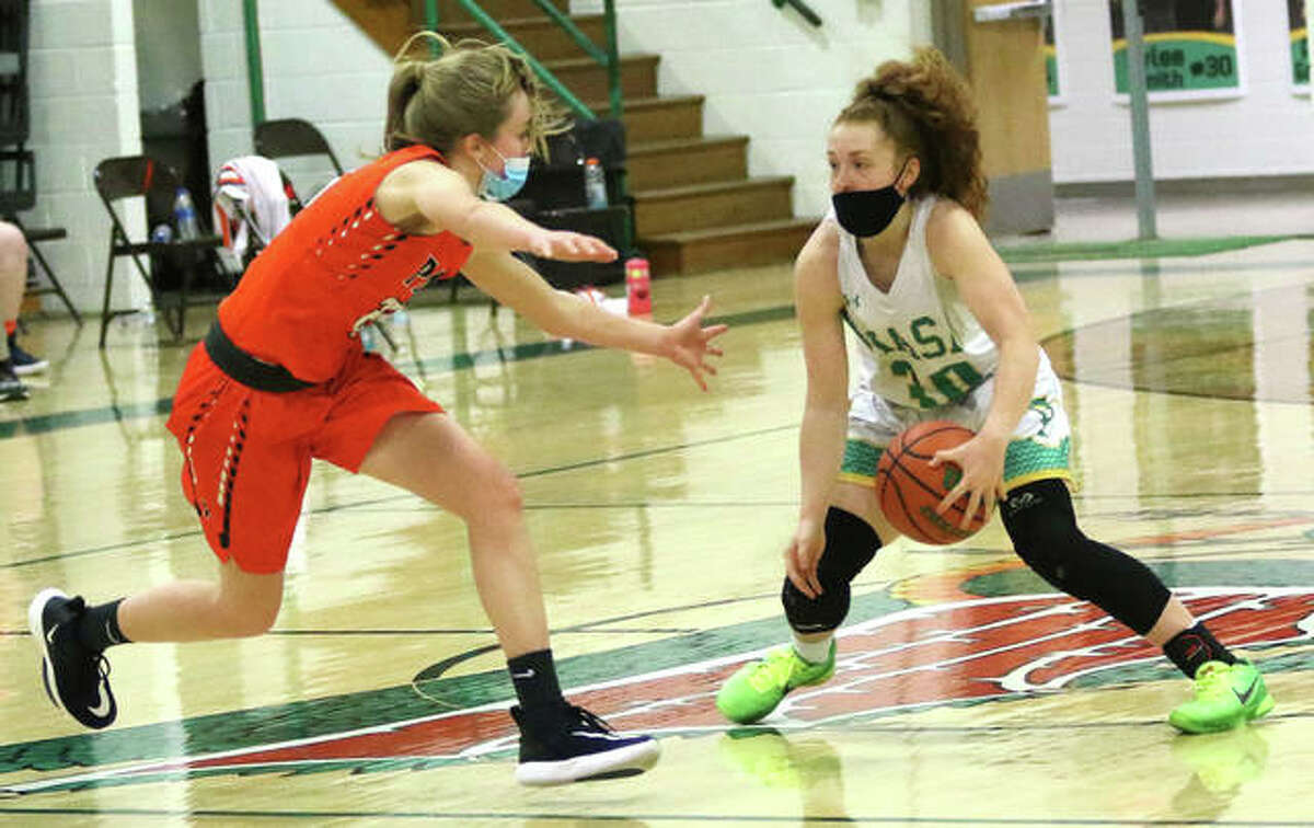 Southwestern point guard Rylee Smith (right) crosses over while Pana's Ellie Kuhn defends Friday night in Piasa.