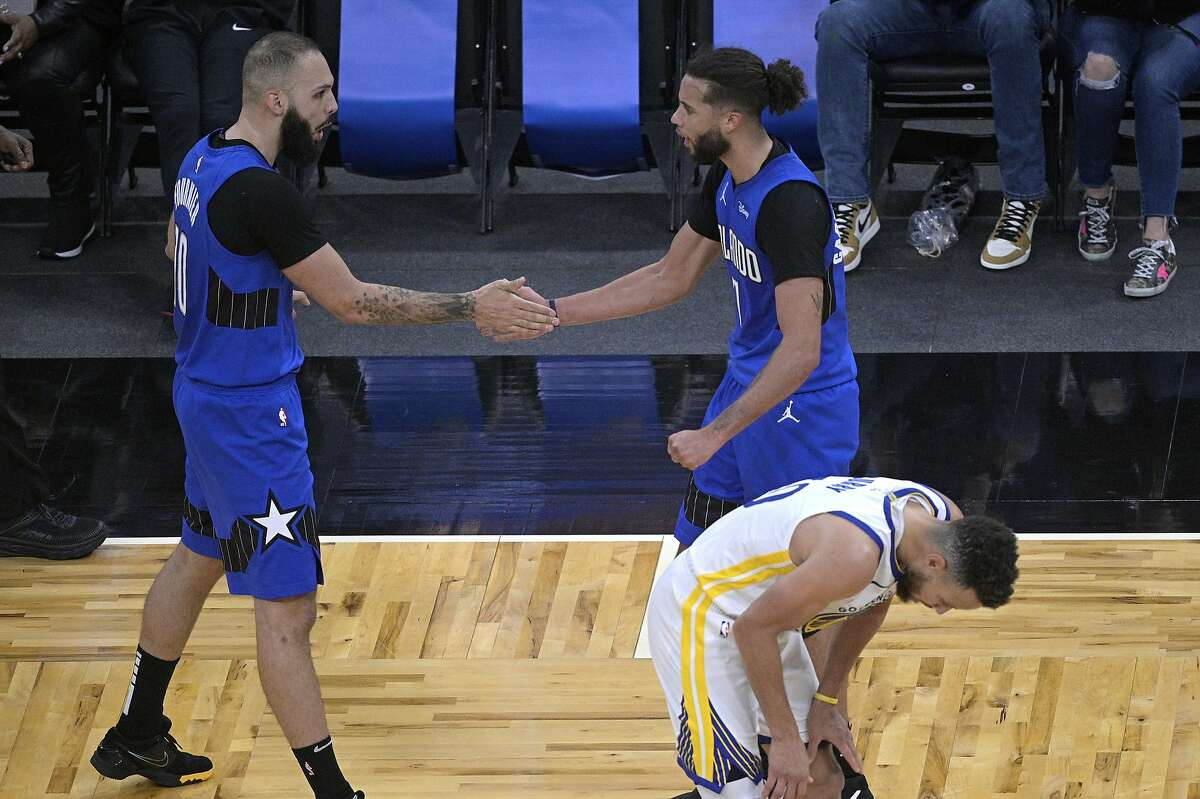 Evan Fournier, left, and Michael Carter-Williams celebrate in front of Stephen Curry in the second half of Orlando's win.