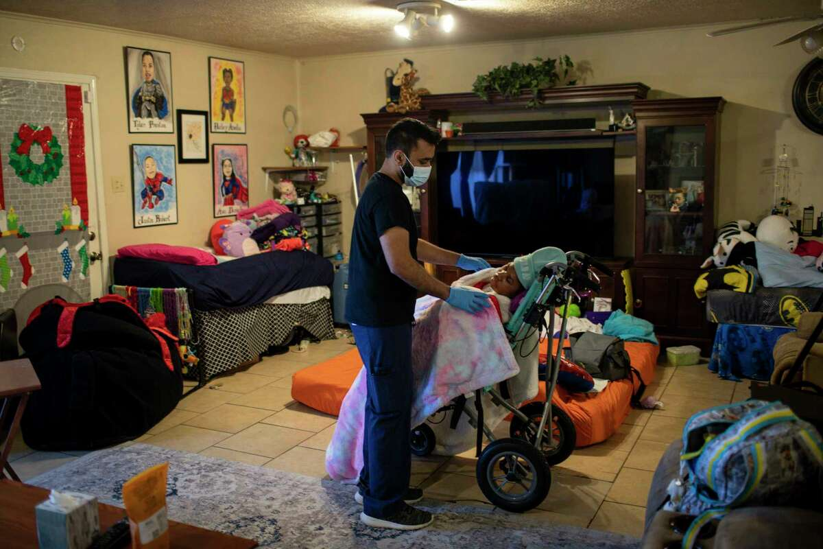 Samir Haq, a home-health nurse, covers Hailey Cheevers, 11, as he gets her settled in her home after she returned following several days of winter storms Friday, Feb. 19, 2021, in Houston. Pipes broke in the cold weather causing parts of the ceiling to collapse.