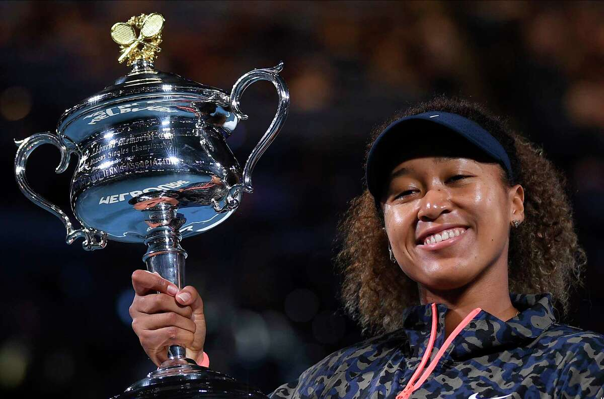 Japan's Naomi Osaka holds the Daphne Akhurst Memorial Cup after defeating United States Jennifer Brady in the women's singles final at the Australian Open tennis championship in Melbourne, Australia, Saturday, Feb. 20, 2021.