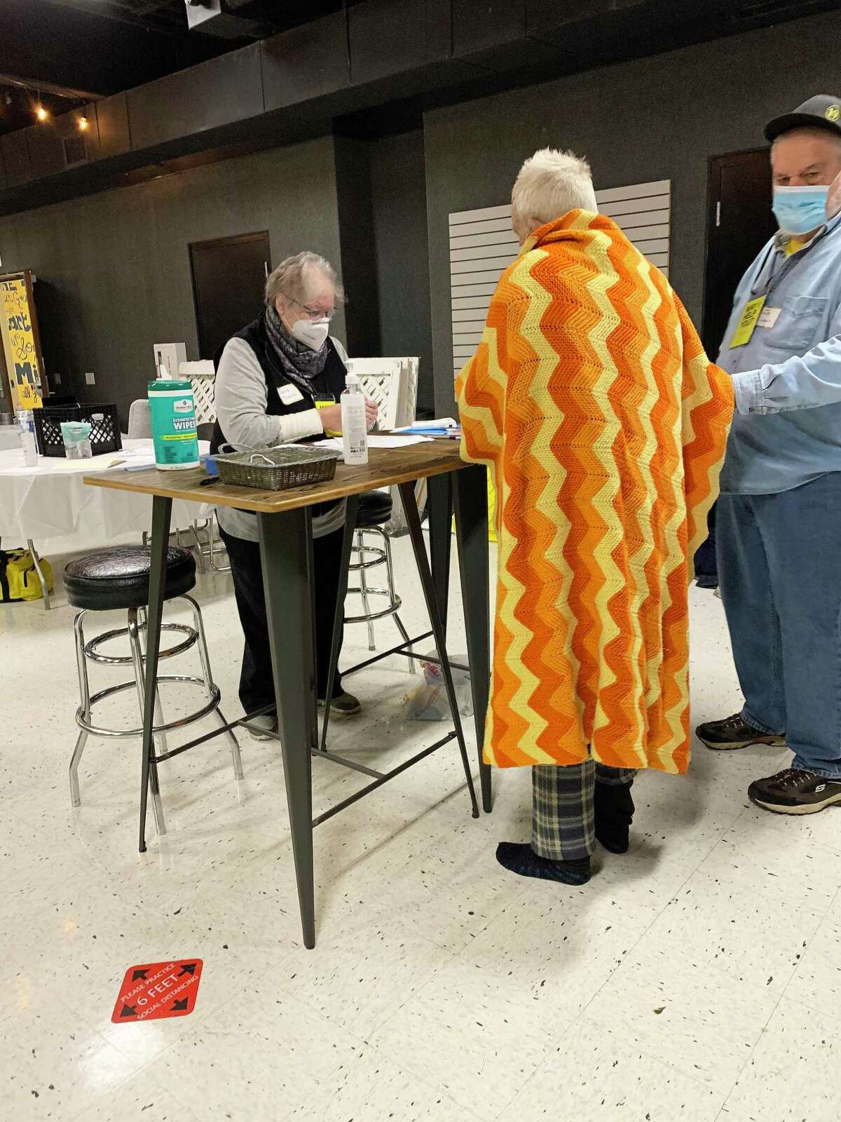 Volunteer Diana Braziel registers a homeless person wrapped in a blanket while he receives assistance to stand from volunteer Joe Lewis. The Foundry United Methodist Church partnered with Cy-Fair Helping Hands to help the homeless and elderly through the frigid weather.