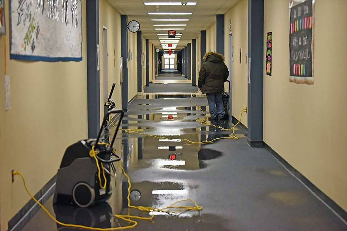 Water is cleaned up from the floor of Swenke Elementary School by restoration crews after the winter storm resulted in pipe damage at the campus.