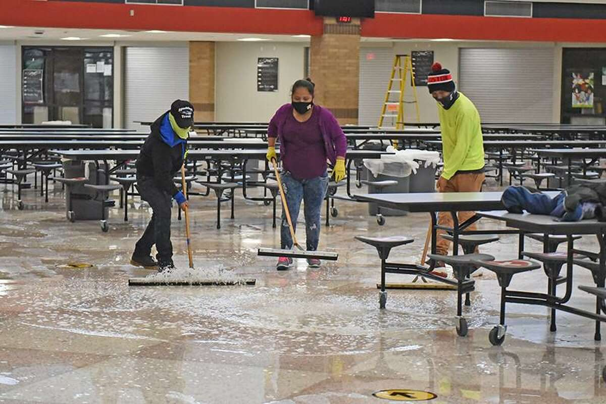 Water is cleaned up from the floor of Langham Creek High School by restoration crews after the winter storm resulted in pipe damage at the campus.