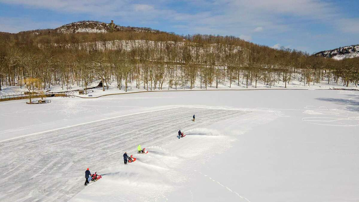 City crews clear a section of Mirror Lake in preparation for public skating at Hubbard Park in Meriden, Conn. Thursday, Feb. 11, 2021. (Dave Zajac/Record-Journal via AP)
