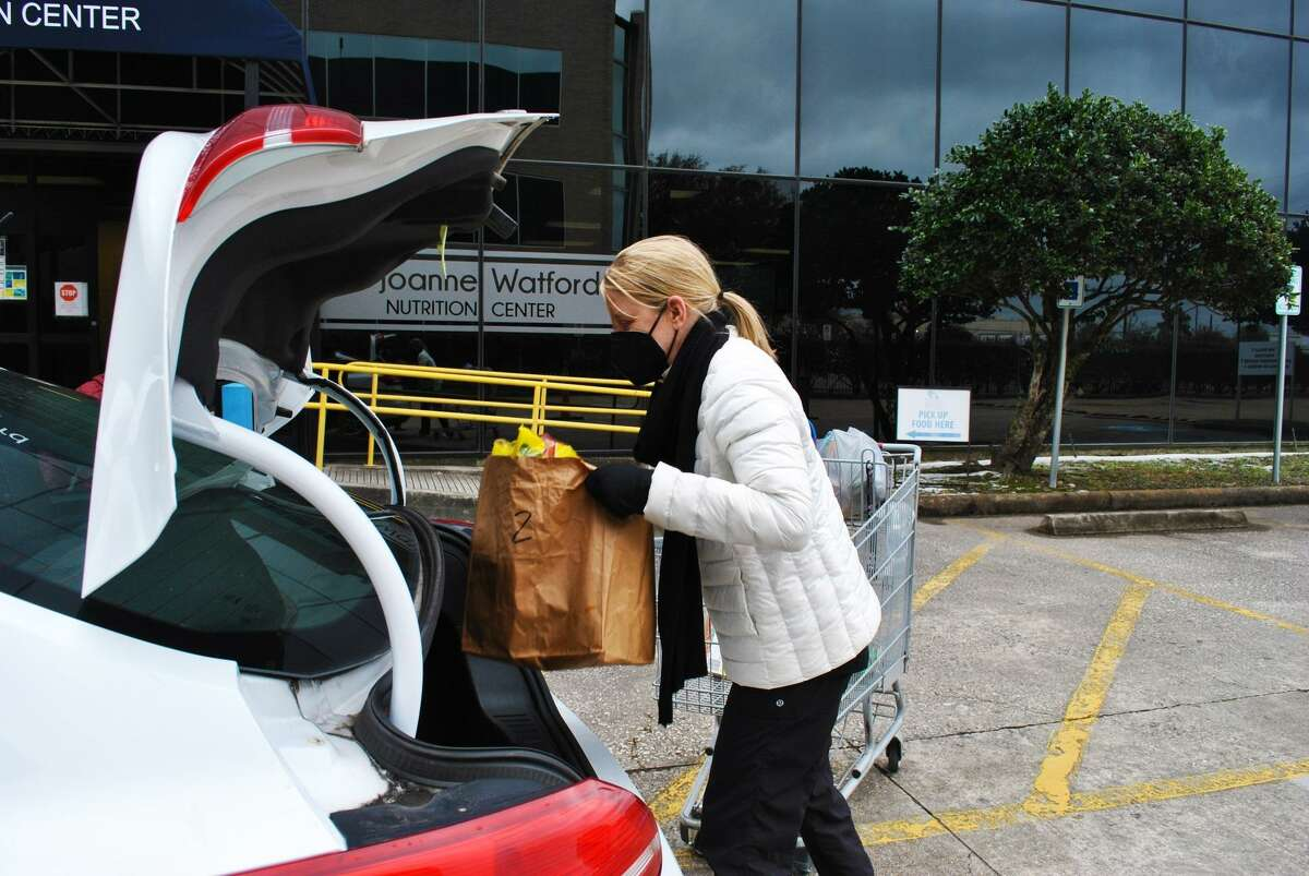 Staff and volunteers with Northwest Assistance Ministries help the nonprofit provide food to community members in need as NAM was able to restart some of its services Thursday, Feb. 18, 2021, during the week of the devastating winter storm.