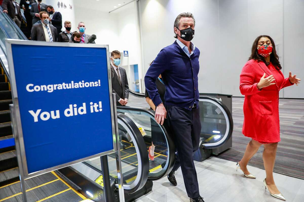 Governor Gavin Newsom (center) and Mayor London Breed (right) get a tour of the Moscone Center vaccination site on Friday, Feb. 12, 2021 in San Francisco, California.